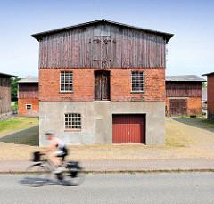 Fassade einer Scheune in Bünningstedt / Ammersbek - ein Teil der Fassade ist mit Holzbrettern verkleidet - ein Rennradfahrer auf der Strasse.