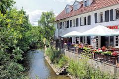 Restaurant mit Terrasse an der Trave in Bad Oldesloe - Bäume am Flussufer, Sonnenschirm.