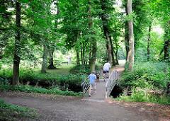 Spaziergänger auf einer Brücke im Glückstädter Stadtpark.