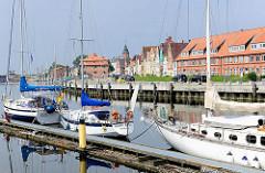 Segelboote im Sportboothafen Glückstadt an der Unterelbe - die Schiffe liegen am Steg im Binnenhafen. Auf der anderen Seite des Hafenbeckens historische Häuser der Stadt.