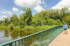 Grüne Brücke über die Trave in Bad Oldesloe - Jogger beim Laufen.