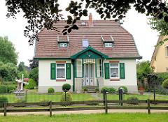Einzelhaus, Wohnhaus in Hoisbüttel / Ammersbek - Architektur Heimatstil; grüne Fensterläden, Holzläden; kleine Windmühle im Garten.