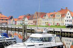 Häuserzeile am Binnenhafen von Glückstadt an der Unterelbe - historische Wohngebäude; Sportboote / Motorboote am Kai.