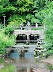 Brücke über die Krückau bei der Barmstedter Schlossinsel - Spaziergänger + Radfahrer auf der Steinbrücke - Bäume auf der Schlossinsel.