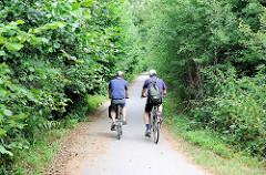 Radweg am Rande des Heidkoppelmoors in Hoiesbüttel / Ammersbek - zwei Radfahrer bei einer Radtour durch das Naturschutzgebiet.