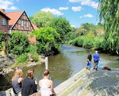 Jugendliche sitzen am Flussufer in Bad Oldesloe, Kreis Stormarn. Fachwerkhäuser am Flussufer.