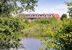 Neubauten in Bad Oldesloe - wohnen im Grünen; See mit Bäumen.
