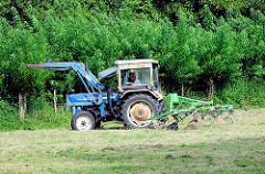 Landwirt mit Traktor beim Wenden von gemähtem Gras auf einer Wiese in Bünningstedt / Ammersbek.