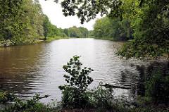 Blick auf den Lottbeker Teich in Hoisbüttel / Ammersbek - die Ufer vom kleinen See sind dicht mit Bäumen und Büschen bewachsen.