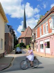 Heiligen Geist Kirche in Barmstedt, Kreis Pinneberg - Radfahrerin in Fahrt; blauer Himmel weisse Wolken.