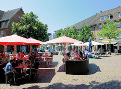 Café / Restaurant in der Fussgängerzone von Ahrensburg / Stormarn; die Gäste sitzen unter Sonnenschirmen im Freien auf dem Strassenpflaster; im Hintergrund die Skulptur Muschelläufer, Künstler Martin Wolke.