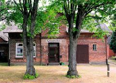 Wohnhaus - Ziegelgebäude, Einfamilienhaus mit Garagentor; über dem Eingang steht die alte Aufschrift GASTWIRTSCHAFT; Fotos aus der Gemeinde Ammersbek / Ortsteil Bünningstedt.