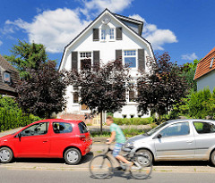 Weisse Stadtvilla in Bad Oldesloe - blauer Himmel weisse Wolken; parkende Autos - Fahrradfahrer.