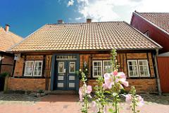 Historische Wohnhaus - Fachwerkhaus in Bad Oldesloe; blühender Fingerhut am Strassenrand.