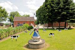 Landarbeiterkate mit Reet gedeckt - Wohnhäuser für Bedienstete des Gut Altfresenburg. Holzwindmühle und Kühe als Dekoration auf der Wiese vor dem Haus.