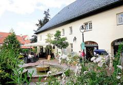 Sprudelnder Brunnen - Einkauszone an der Trave; Restaurant mit Aussengastronomie in der Hude.