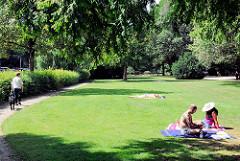 Grünanlage, Wiese am Rantzauer See in Barmstedt - ein Pärchen sitzt auf einer Decke in der Sonne - Spaziergängerin mit Hund.
