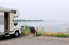 Stellplätze für Wohnmobile am Hafen Glücksstadt - eine Besucherin der Stadt sitzt neben ihrem Wagen im Campingstuhl und liest die Zeitung - im Hintergrund die Einfahrt zur Unterelbe.