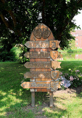 Holzschild mit deutschen Städtenamen in Polen an der Stolpmünder Eiche in Glückstadt.