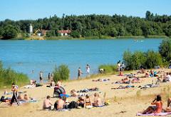 Badestelle Tangstedt - Kiesgrube mit Sandstrand; Badegäste liegen auf Handtüchern und Decken in der Sonne.