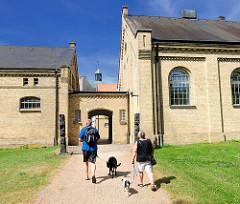 Ehem. Stallgebäude Schloss Gottorf in Schleswig - Besucher mit angeleinten Hunden.