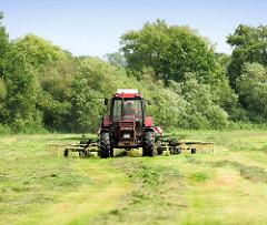 Heuernte in der Gemeinde Tangstedt / Kreis Stormarn. Traktor mit Heuwender bei der Arbeit.