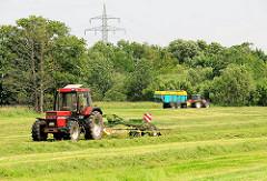 Heuernte in der Gemeinde Tangstedt / Kreis Stormarn. Ein Traktor wendet das Gras - im Hintergrund Traktor mit Anhänger, der das Heu während der Fahrt aufnimmt.
