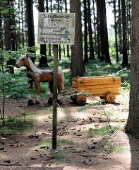 Tangstedter Forst - Naturerlebnisstation; Waldarbeiter auf vier Hufen; Holzskulptur Pferd und Wagen. Hinweisschild Justizvollzugsanstalt Glasmoor -  Bilder aus der Gemeinde Tangstedt, Kreis Stormarn.