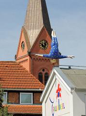 Kirchturm der St. Ansgarkirche mit Kirchenuhr in Schleswig - tanzende Figur vom Puppentheater Trauminsel.