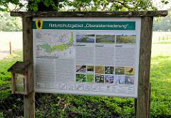 Hinweisschild Naturschutzgebiet Oberalsterniederung - Erklärung von Fliesgewässer, Hochmoore und Grünland.