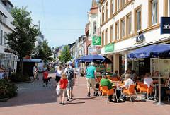 Fussgängerzone Stadtweg in Schleswig - Tische eines Cafès stehen auf dem Weg in der Sonne - Gäste sitzen an Tischen und beobachten die Passanten.
