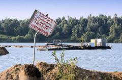 Saugbagger zur Gewinnung von Sand - Warnschild mit roter Schrift; Aufenthalt im Arbeitsbereich des Saugbaggers verboten.