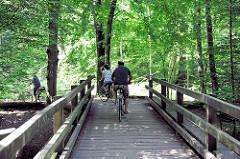 Holzbrücke mit Radfahrern über die Alster - Wald bei Wulksfelde, Gemeinde Tangstedt - Kreis Stormarn.