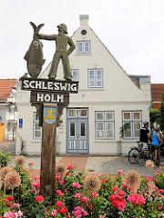 Geschnitztes Holzschild - ein Fischer hält einen großen Fisch - Inschrift Schleswig Holm; ein Fischerviertel.