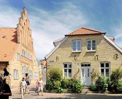 Historische Architektur in Schleswig - Hausfassade mit Jahreszahl 1773 - Touristen gehen durch die engen Gassen.