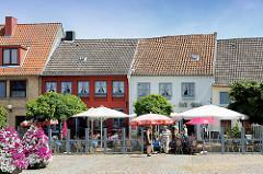Aussengastronomie auf dem Rathausmarkt in Schleswig - Restaurants haben Tische auf den Platz gestellt - die Gäste sitzen unter Sonnenschirmen im Freien.