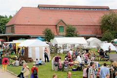 Bauernmarkt auf dem Biogut Wulksfelde - Zelte und Gebäude mit Ziegeldach.