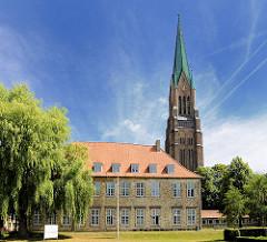 Kirchturm vom St. Petri Dom in Schleswig.  Im Vordergrund die historische Architektur vom Bischofshof / Bischofsplast; erbaut Mitte des 15. Jhd.