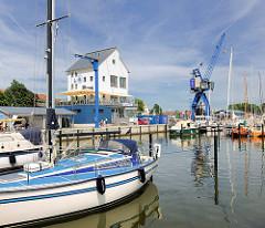 Hafenspeicher und Kran - Sportboothafen in der Stadt Schleswig. Segelboote liegen am Steg; blauer Himmel mit Schleierwolken.