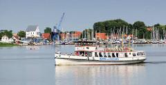 Fahrgastschiff Wappen von Schleswig auf der Schlei bei - im Hintergrund der Sportboothafen, ehem. Speichergebäude und Hafenkran vom Hafen der Stadt Schleswig.