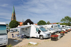 Weisse Wohnmobile stehen am Hafen der Stadt Schleswig - im Hintergrund der Turm vom St. Petri Dom.