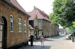 Historische Gebäude am St. Petri Dom der Stadt Schleswig - ein Fotograf mit Stativ macht eine Aufnahme.