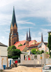 Moderne Baustelle eines Wohnhauses in Schleswig - Bauarbeiter bei der Arbeit - im Hintergrund das historische Gebäude vom St. Petri Dom - romanisches Querschiff erbaut um 1200.
