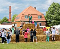 Gut Wulksfelde - Bauernmarkt; aufgestapelte Strohballen, Kinder spielen - Gebäude der Gutsküche.