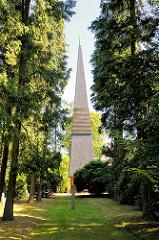 Kirchturm der Tangstedter Kirche zwischen Bäumen.