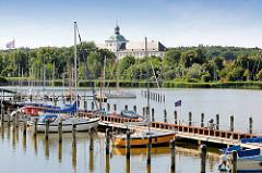Sportboothafen an der Schlei in Schleswig - im Hintergrund das Gottorfer Schloss zwischen Bäumen.