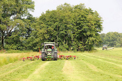 Heuernte mit zwei Traktoren - wenden von gemähtem Gras; Wiesen in der Gemeinde Tangstedt, Kreis Stormarn.