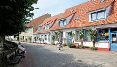 Wohnhäuser / Fischerhäuser an der Norderholmstrasse in Schleswig - Kopfsteinpflaster - Rosenstöcke mit blühenden Rosen an den Hausfassaden - Sitzbänke.