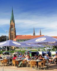 Aussengastronomie am Hafen Schleswigs - Restaurant mit Tischen und Sonnenschirmen  auf der Hafenpromenade - Gäste sitzen in der Sonne - im Hintergrund das Kirchengebäude vom St. Petri Dom.