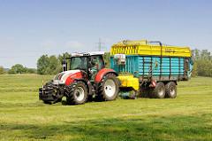 Heuernte in der Gemeinde Tangstedt / Kreis Stormarn. Ein Traktor mit Hänger nimmt das getrocknete Gras auf.